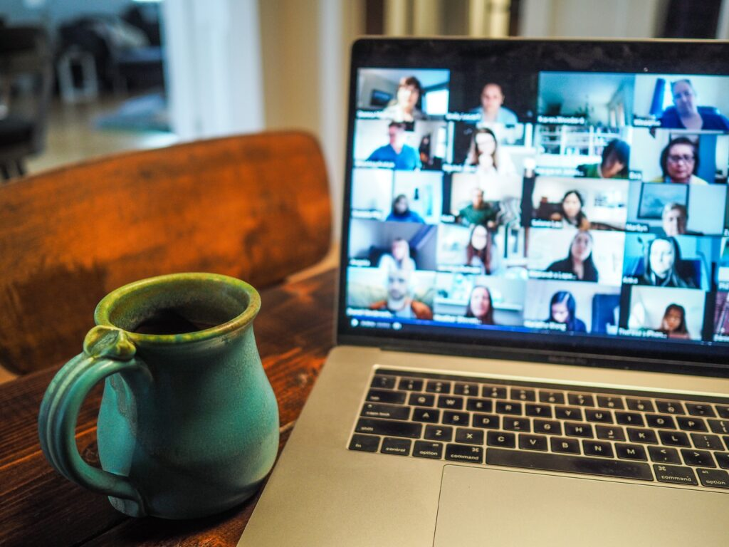 laptop with zoom meeting on the screen and coffee cup beside it